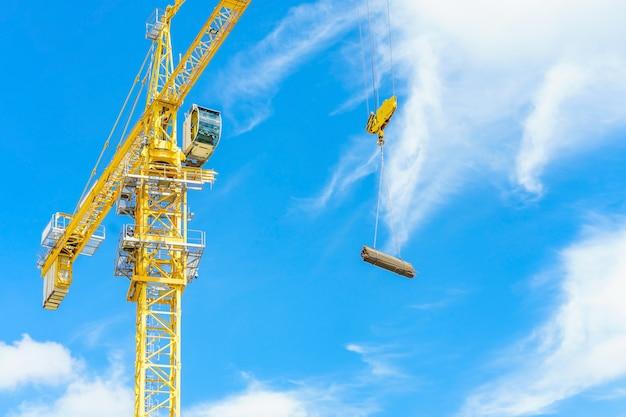 建設用クレーンと青い空を背景に建設中の高層ビル。