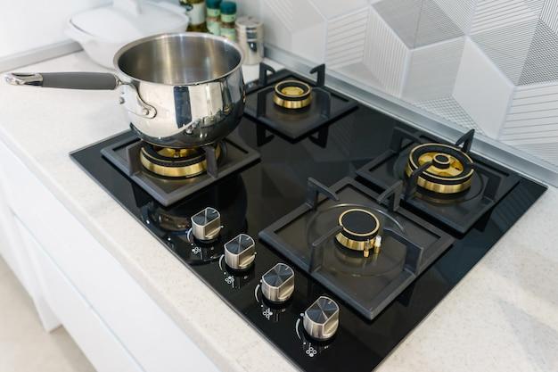 Металлический горшок на индукционной плите в современной кухне