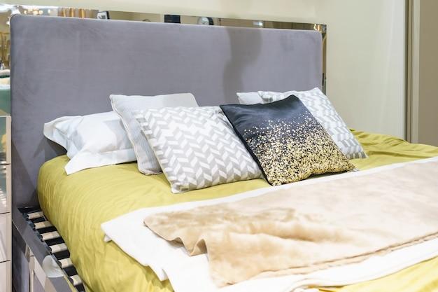 Современная спальня с набором подушек на классической кровати, концепция дизайна интерьера