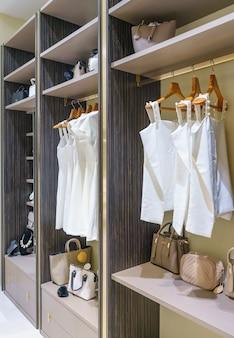 クローゼットのデザインインテリアで散歩にレールに掛かっている服を着てモダンな木製ワードローブ