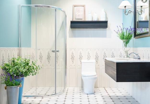 ガラス張りのシャワー、トイレ、シンク付きの明るいタイル付きのモダンな広々としたバスルーム。側面図