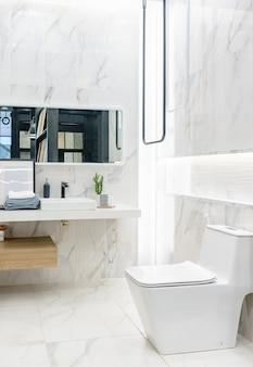 白い壁、ガラス張りの壁があるシャワーブースのある明るくモダンなバスルームのインテリア