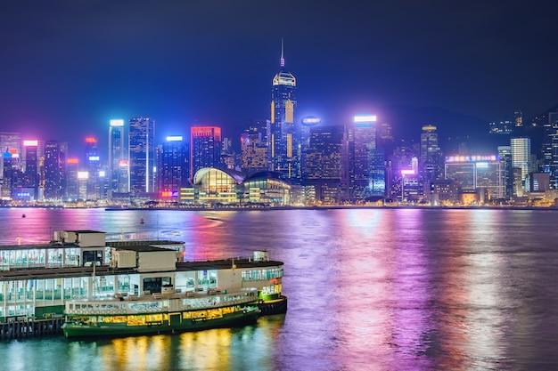 Небоскребы городского пейзажа горизонта гонконга городские над гаванью виктории в вечере. гонконг, китай