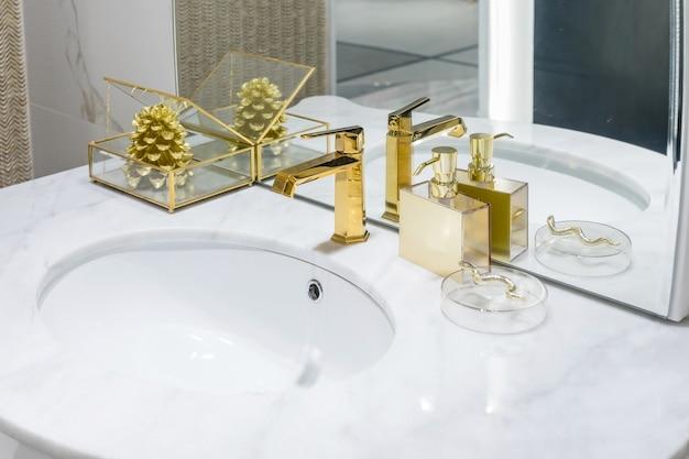 白い洗面台と古典的なレトロスタイルの黄金の蛇口付きのバスルームの高級クラシックインテリア