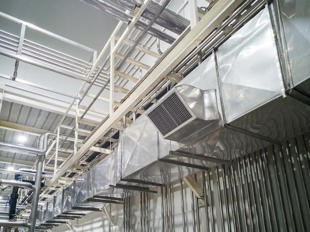工業ビルの天井に設置された工業用エアダクト換気装置およびパイプシステム。