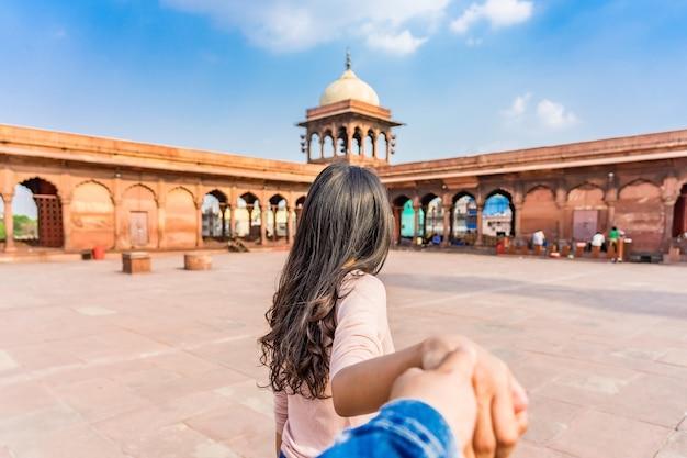 アジアの若い女性観光客は、インドのオールドデリーの赤いジャマモスクに男をリードします。一緒に旅行します。フォローしてください。