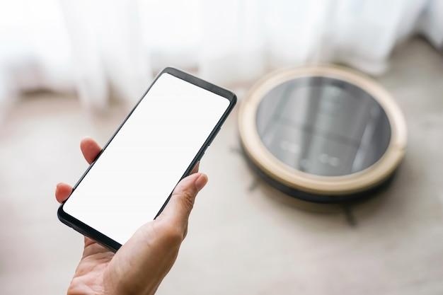 モバイルアプリケーションを使用してクリーニングを開始するロボット掃除機を制御するスマートフォンを保持している女性