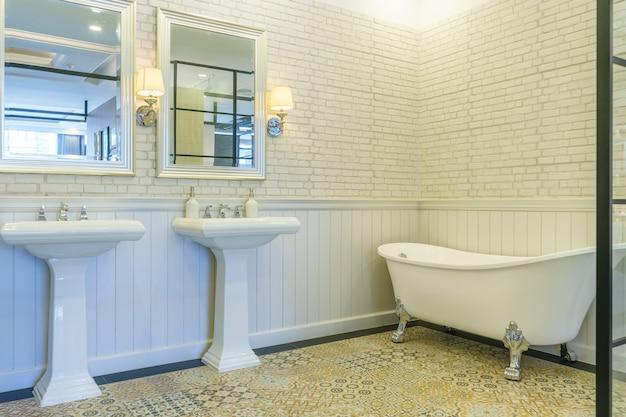 照明、白いトイレ、洗面台、バスタブ付きのモダンなバスルームのインテリア
