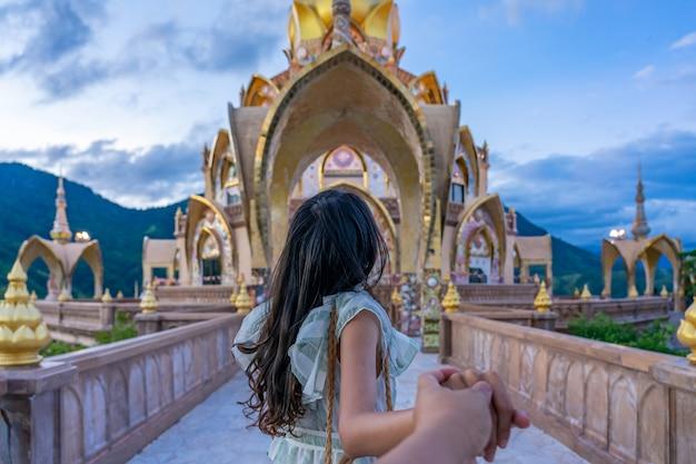 タイのペッチャブーンにあるワットプラタットパーソンケオ寺院の主塔のビューに彼氏を導く若い女性旅行者。