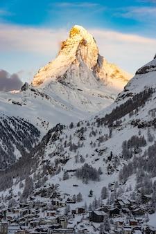 スイス、ツェルマットの村の日の出の直前に、スイスアルプスのマッターホルンの先端に太陽が輝いています。