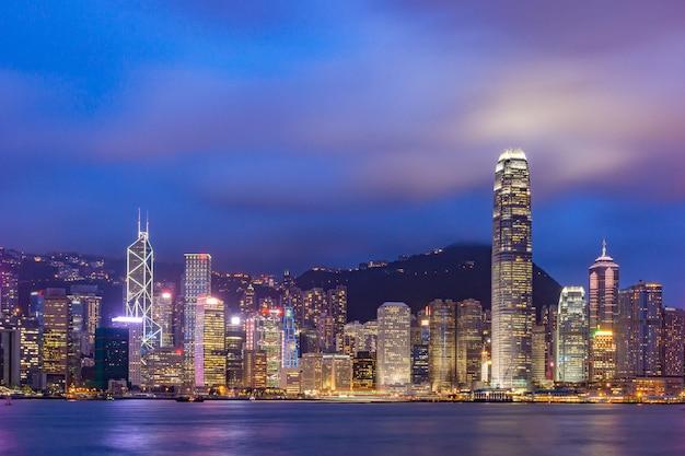 夕方にはビクトリアハーバーの上の香港のスカイラインの街並みのダウンタウンの高層ビル。香港、中国