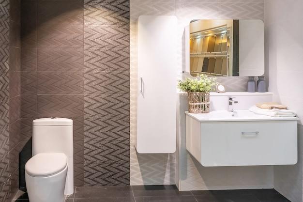 白い壁、ヴィンテージ家具、タオル、トイレ、洗面台付きのバスルームのインテリア