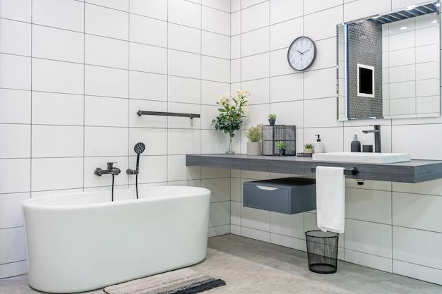 ミニマルなシャワーと照明、白いトイレ、洗面台、バスタブを備えたモダンなバスルームのインテリア