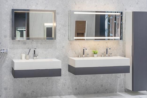 トイレと洗面台付きの明るいタイルを備えたモダンな広々としたバスルーム。側面図
