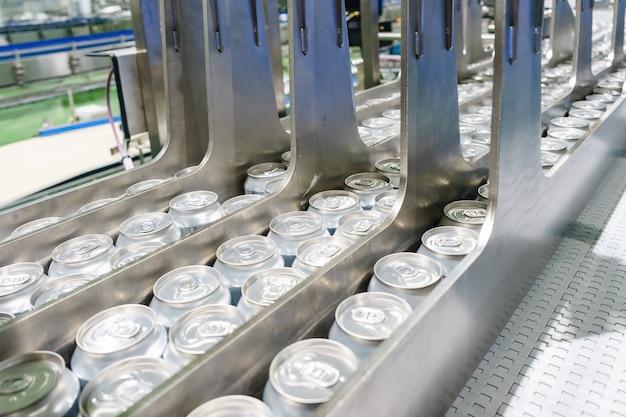 工場で何千ものアルミニウム飲料缶を運ぶコンベアライン