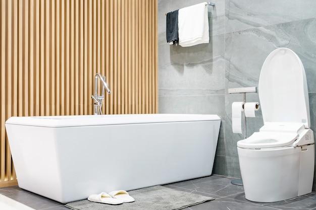 最小限のシャワー、白いトイレ、シンク、バスタブ付きのバスルームインテリア
