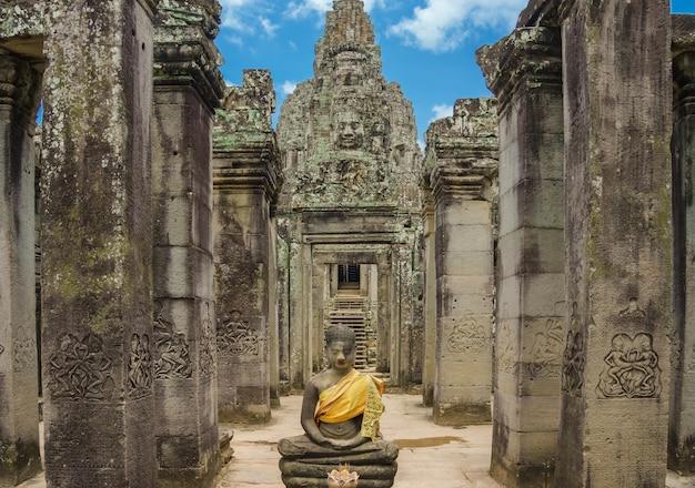 古代の石は、バイヨン寺院、アンコールワット、サイアムレープ、カンボジアの曇りの青い空に顔を当てる。