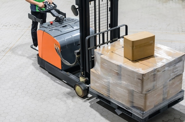 倉庫内のパレットにある箱付き電気フォークリフトトラック
