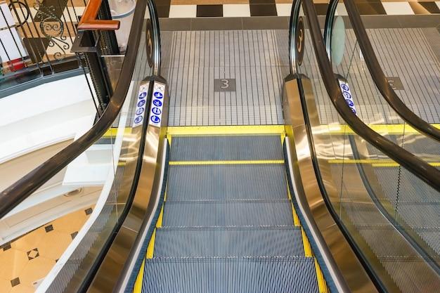 ショッピングセンターのコミュニティモールにあるエスカレーター。階段を上がる。電気エスカレーター。