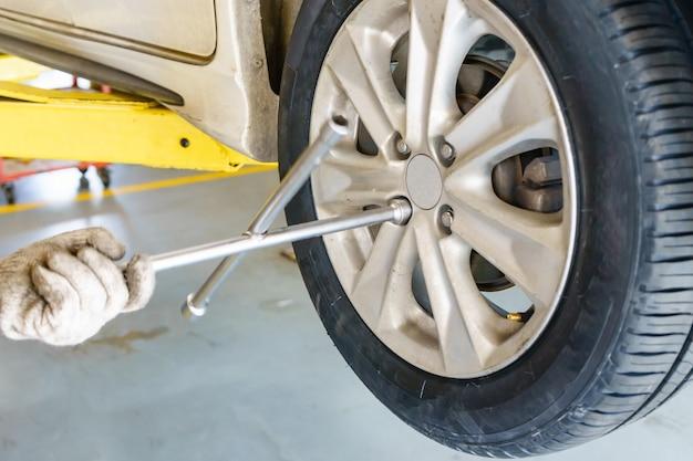 ワークスでタイヤを交換する電動ドライバーを持つ自動車整備士