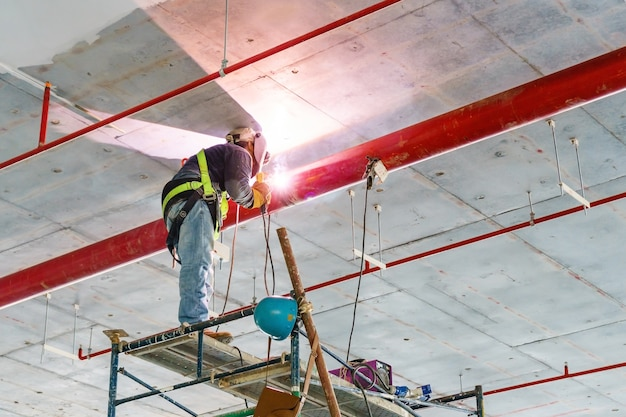 完成していない新しい建物の内部で天井から垂れ下がっている赤いパイプを溶接する作業員
