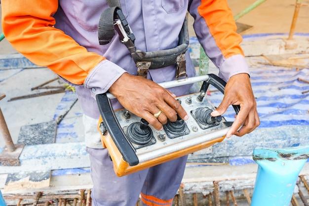 金属棒補強のトレーラーに取り付けられたブームコンクリートポンプを制御する作業員