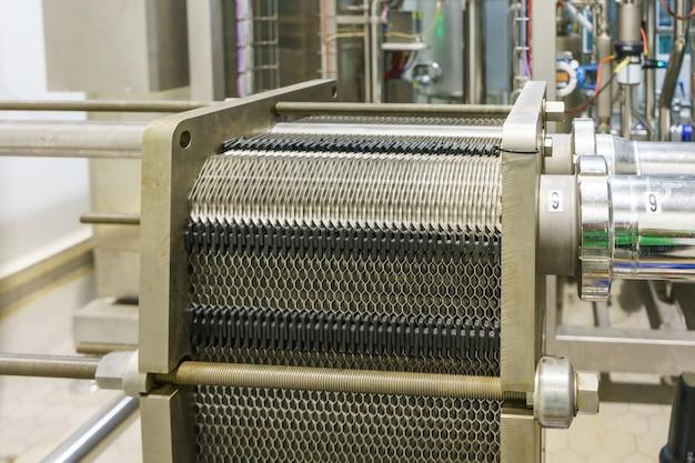熱交換機の金属板と食品産業プラントのポンプ