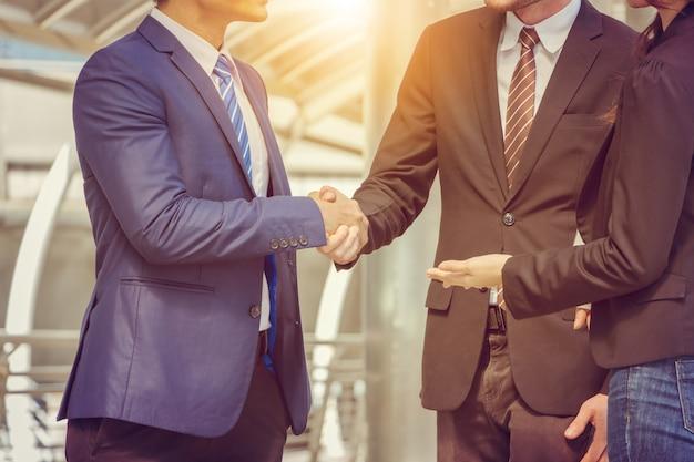 彼らの隣に立っている経済人とビジネスマンの握手