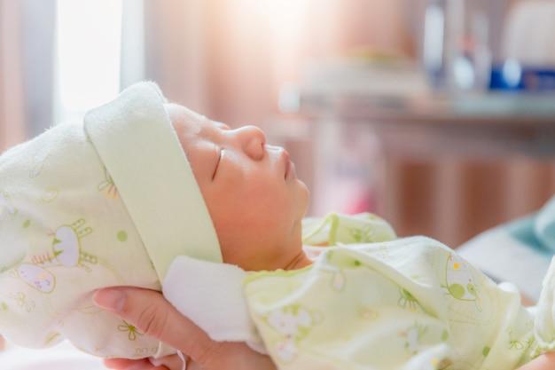 病院でアジアの母親の手で寝ている生まれたばかりの赤ちゃんの男の子