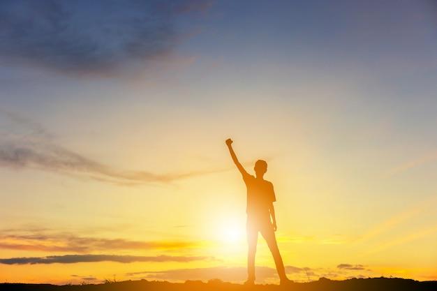 山の頂上夕方の空夕日を背景に男のお祝いの成功幸福のシルエット。