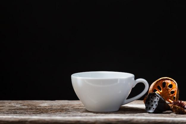 木製の暗い背景に白いカップ乾燥マルメロとシナモンの棒