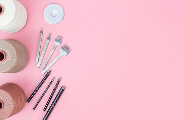Группа инструментов из кожи с восковой веревкой и пуншем на розовом фоне