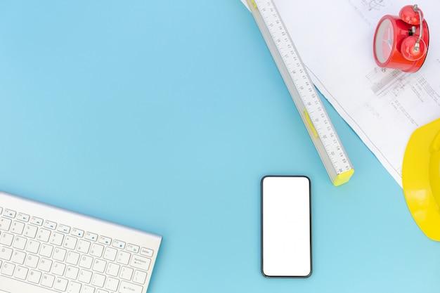 エンジニアリングツール、コンピューターのキーボード、スマートフォン、青写真、ヘルメット、測定タップ、フラットレイアウトのコピースペースを持つトップビュー
