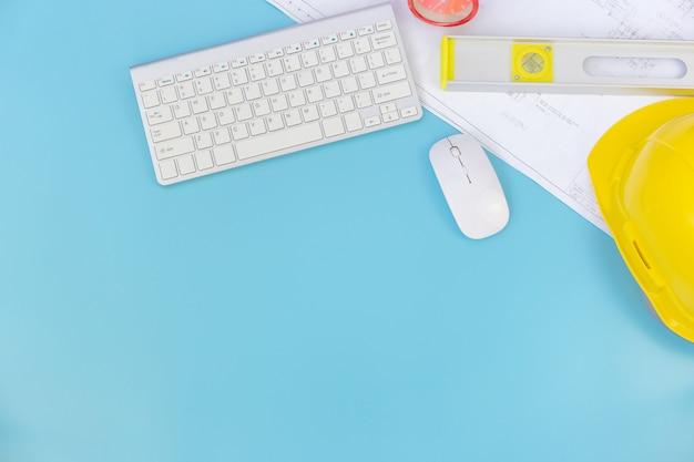 エンジニアリングツールとコンピューターのキーボード、青写真、ヘルメット、測定テープ、フラットレイアウトコンセプトのコピースペースを持つトップビュー