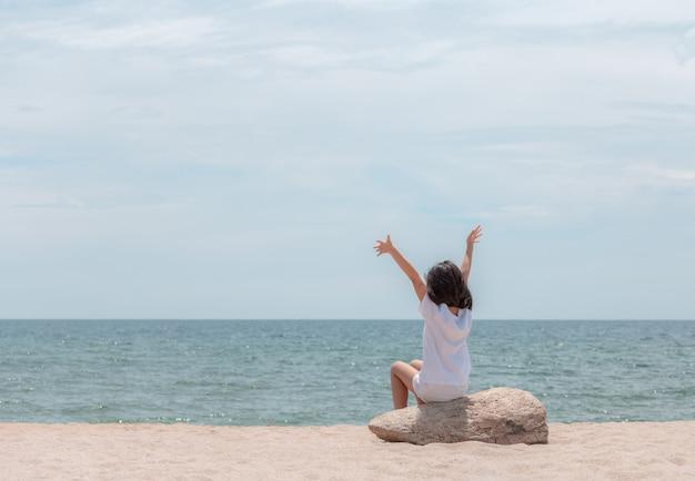 Счастливый маленькая девочка сидит с распростертыми объятиями и видом на море на пляже