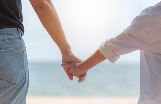 Вид сзади матери и дочери, взявшись за руки и видом на море