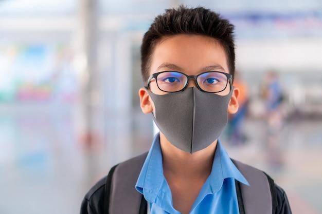 Мальчик в школьной форме нося хирургическую маску с запачканной предпосылкой, концепцией предохранения от вируса.