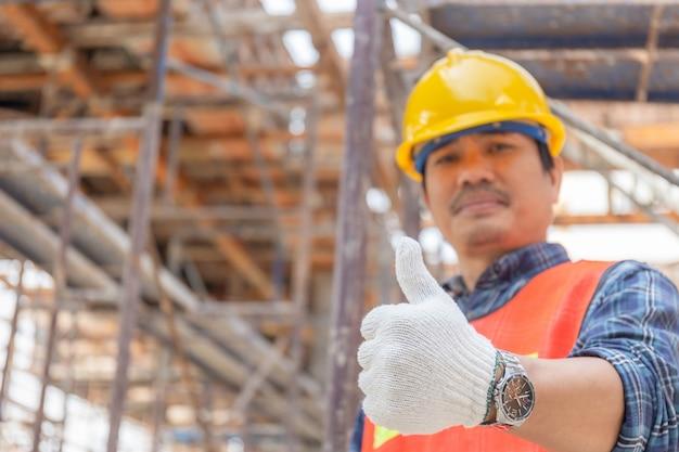 Рука человека инженера / работника давая большой палец руки над запачканной строительной площадкой, успешной концепцией