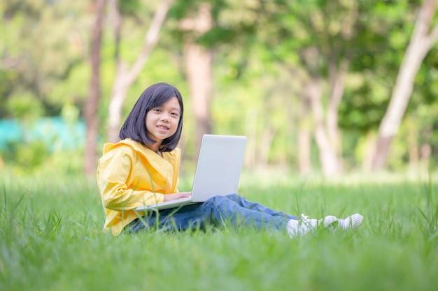 草の上に座っている笑顔の女の子