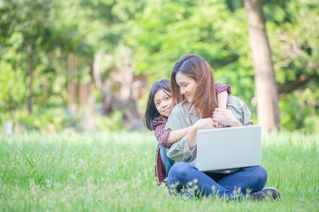 母と娘は草の上に座って