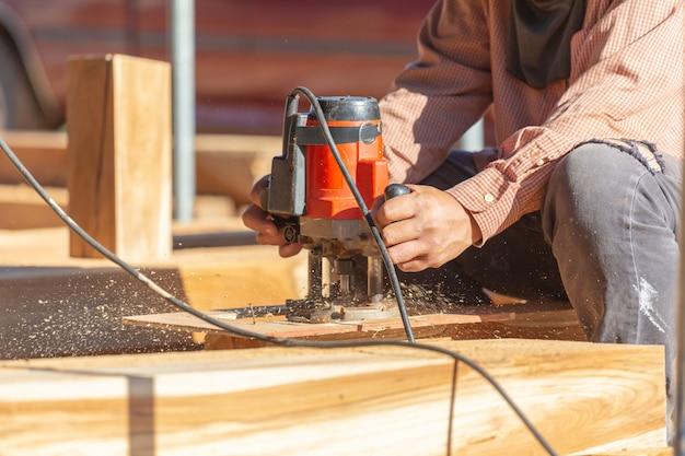 木の板を研削大工の手のクローズアップ、のこぎりに取り組んで木を切った。