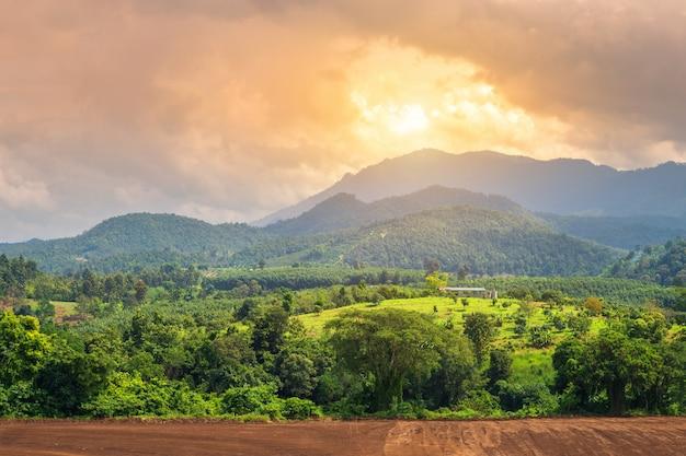 Красивый заход солнца в ландшафте деревни гор в сельской местности.