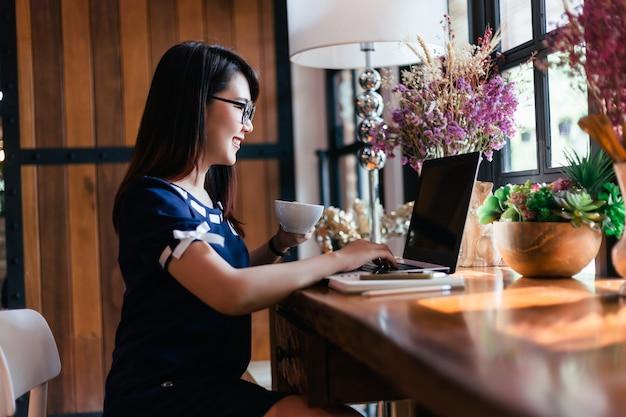アジアのビジネス女性は背景のようなコーヒーショップでノートパソコンでの作業のマグカップを保持します。