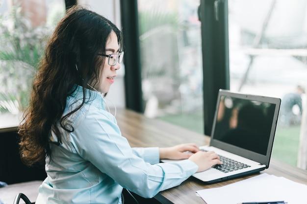 ビジネスアジアの女性は、スマートフォンとラップトップコンピューターのイヤホンに身を包んだ