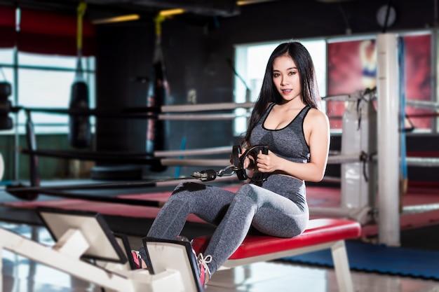 ローイングマシンでエクササイズトレーニングを行うフィットネスアジアの女性