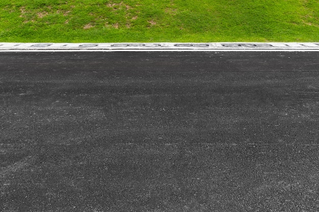 Асфальтовая дорога с полосами и зеленой травой текстуры фона