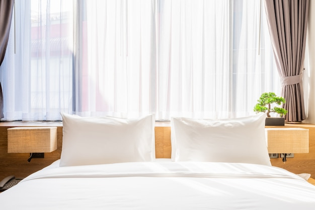Белая подушка на украшении кровати со светлой лампой и зеленым деревом в вазонах в спальне отеля