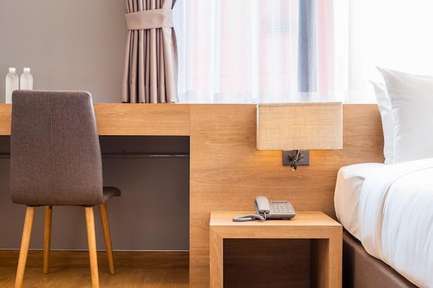 Белая подушка на отделке кровати с лампочкой и цифровым телефоном в спальне отеля