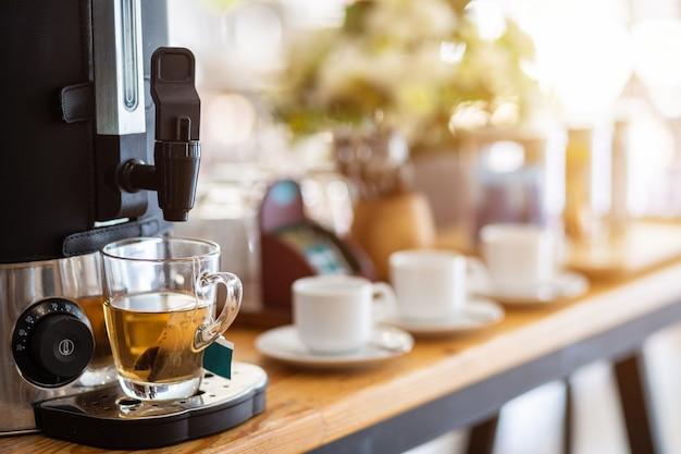 コーヒーメーカーとダイニングテーブルの装飾の上のコーヒーカップからお茶