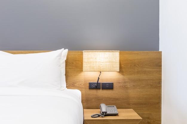 Белая подушка на кровати с лампой и салфеткой в интерьере спальни отеля